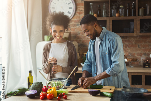 Tela Laughing black couple preparing salad in kitchen