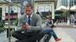 Businessman sitting on street bench and finish texting on cellphone