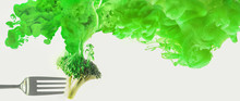 Fresh Broccoli On A Fork With A Cloud Of Dissolving Color. Artistic Nutrition Concept. Science Of Food Action Photography.