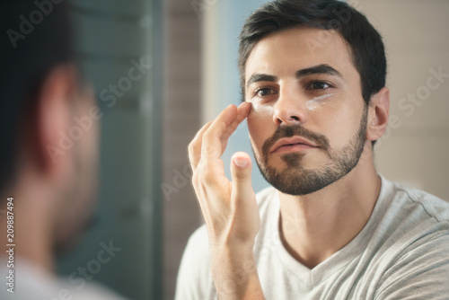 Fototapeta  Young Man Applying Anti-aging Lotion fot Skin Care