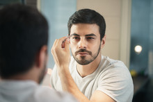 Latino Man Trimming Eyebrow For Body Care In Bathroom
