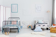 Minimal bedroom interior for two children. Metal frame beds, some toys and posters of a rabbit, an elephant and a whale on a white wall. Real photo