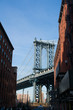 A view of Manhattan Bridge from between two buildings in Brooklyn