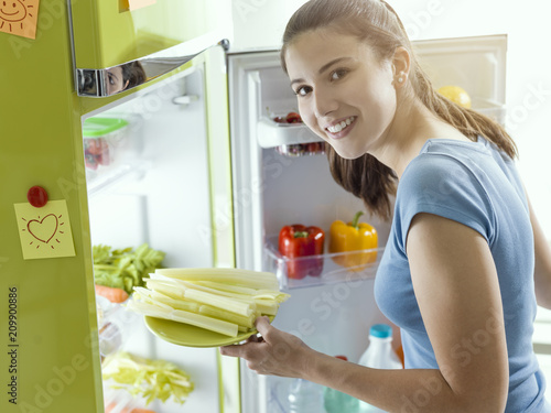 Woman taking fresh celery from the fridge