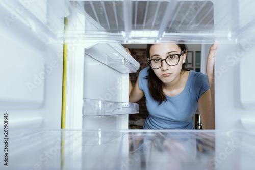 Valokuva Sad woman looking into her empty fridge