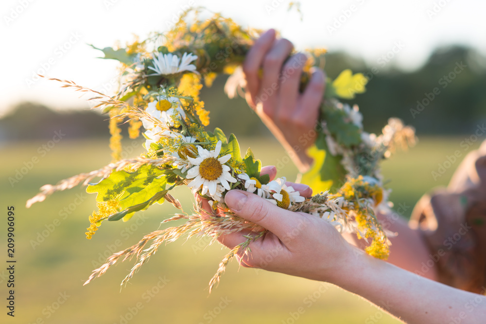 Fototapeta Midsummer in Latvia: celebration of Ligo - a young woman weave a wreath and collect field flowers