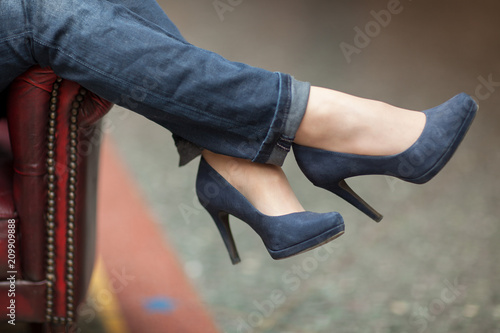 Fotografía  young woman's feet and legs close up in a street cafe, urban mood, blue jeans an