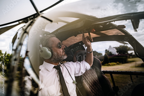 Fotografie, Tablou Pilot starting the controls on helicopter