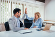 Successful business colleagues giving high five in office.