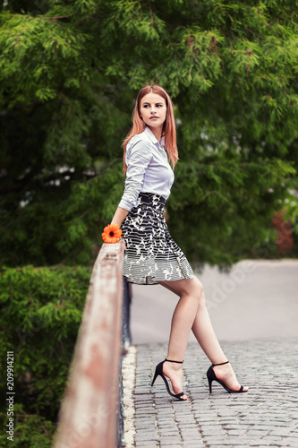 1ee5d56799 Stylish portrait of a beautiful young woman in a black and white skirt on a  sunny day posing and smiling. Happy woman in park, sitting on a bridge.