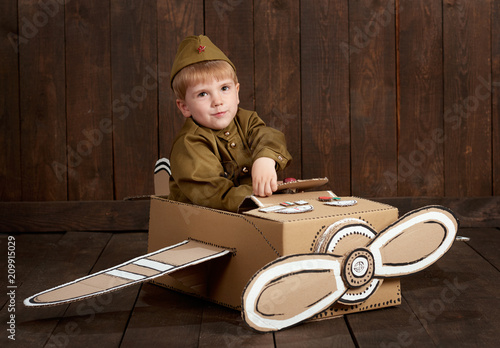 Fotografie, Obraz  children boy are dressed as soldier in retro military uniforms sit in an airplan