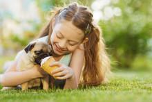 Little Boy Kid Feeding Pug Dog On Summer Day
