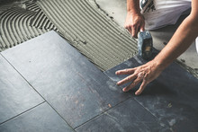 Worker Placing Ceramic Floor T...
