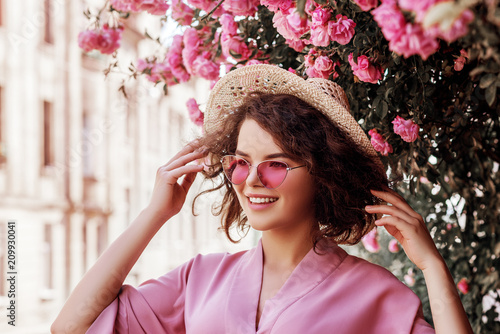 Outdoor close up portrait of young beautiful happy smiling curly girl wearing stylish pink sunglasses, straw hat, dress. Model posing in street near blooming roses. Summer fashion concept