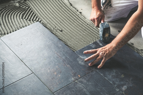 Worker placing ceramic floor tiles on adhesive surface, leveling with rubber hammer
