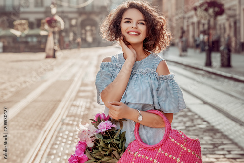 Outdoor portrait of young beautiful happy smiling woman posing in street of european city. Model wering striped dress, wrist watch, holding straw bag with peonies. Copy, empty space for text