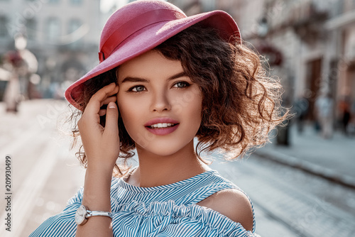 Outdoor close up portrait of young beautiful fashionable curly woman wearing stylish pink hat, elegant wrist watch, posing in street of european city