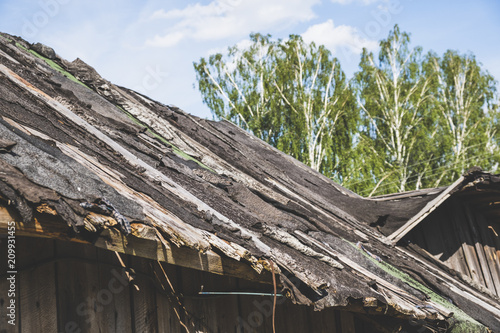 A dilapidated, collapsing village roof. Fotobehang