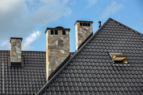 Fotografija Log house in the mountains with a roof made of tiles and stone chimneys