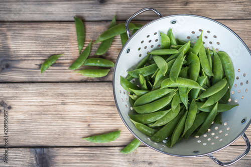 Foto sugar snap peas in a white colander on a wooden table