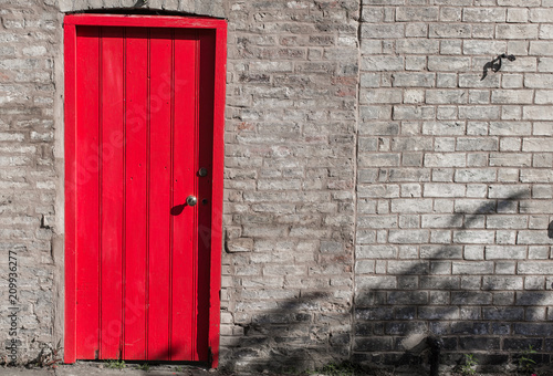 Poster London Closed wooden door bright red on a brick wall