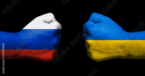 Canvas Print Flag of Ukraine and Russia painted on two clenched fists facing each other on bl