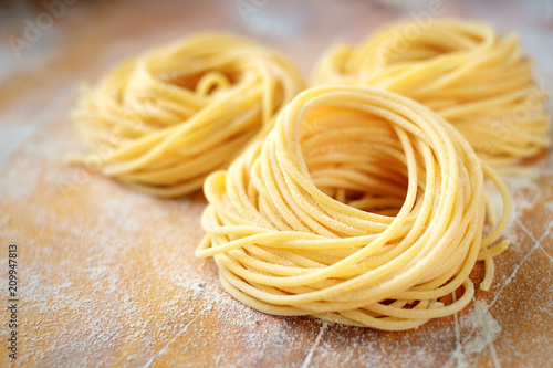 raw homemade spaghetti nest with flour on a wooden table Canvas