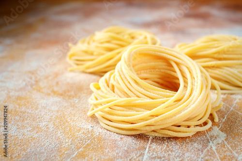 Carta da parati raw homemade spaghetti nest with flour on a wooden table