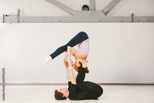 Valokuva  A young Caucasian male and female couple practicing acrobatic yoga in a white gym on mats