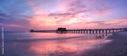 Fotobehang Lichtroze Pink and purple sunset over the Naples Pier