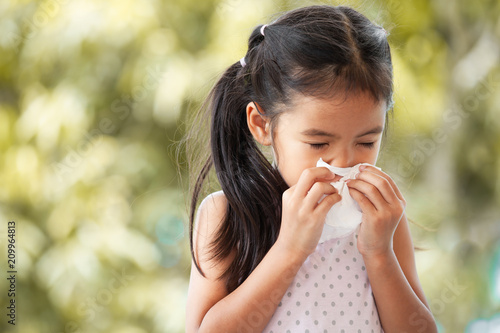Sick asian little child girl wiping and cleaning nose with tissue on her hand Canvas Print