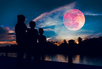 Silhouette of mother with children looking at red super moon on sky.
