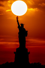 Sun Behind Statue Of Liberty