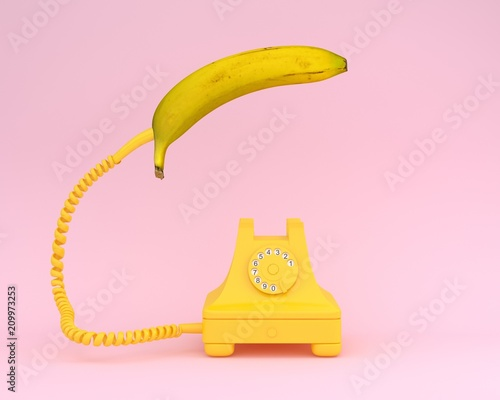 Single banana headphone with yellow retro telephone on pink background.  Fruit minimal concept.