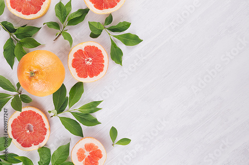 Fruits colorful fresh background - slice grapefruit and green leaves on white wood board.