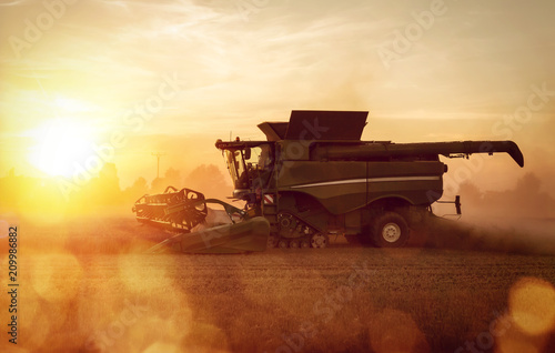 Leinwand Poster Mähdrescher auf dem Feld bei Sonnenuntergang