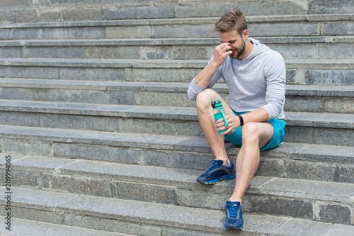 Fotobehang Ontspanning Tired after training on fresh air. Stay hydrated and healthy. Macho with water bottle sit on steps, copy space. Thirst. Strong man with plastic flask relax on stairs. Sport and fitness