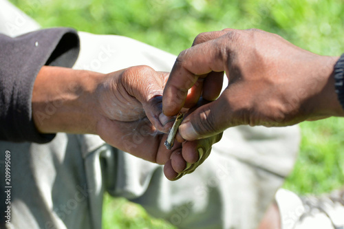 Fotografie, Obraz  Two black hands of South African male smokers exchanging cigarette outdoors on a sunny day
