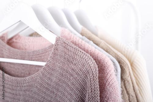 Fényképezés Warm knitted, autumn, winter clothes hanging on a rack, trending concept,pastel