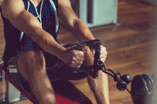 Foto op Plexiglas Fitness Close-up shot of young muscular man doing exercise on rowing machine at modern gym while having intensive workout