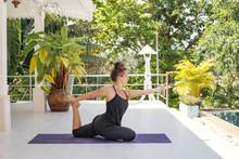 Woman Practicing Yoga On Terra...