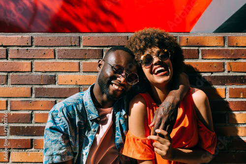 Happy black couple looking at camera in a sunny day
