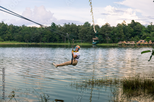 Young woman crossing a lake in zip line