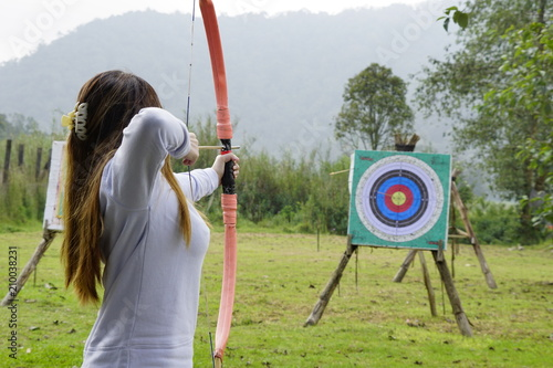Young woman is aiming in archery  practice n the field with a target in front of her Fototapete