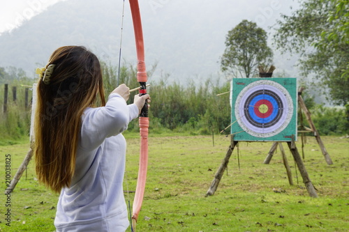Leinwand Poster Young woman is aiming in archery  practice n the field with a target in front of her