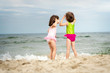 two little girls sisters are standing and playing on the sand at the beach on a summer day