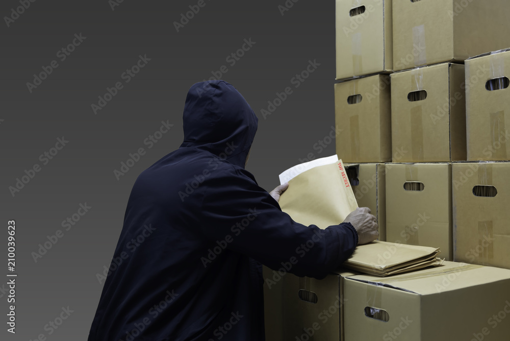 Fototapeta Man wear long sleeves with hood seeking and looking top secret document in the carton. Act like a thieve  or spy secret.