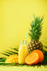 Fototapeta Owoce Delicious juicy smoothie with orange fruit, mango, pineapple on yellow background. Copy space. Pop art design, creative summer concept. Fresh juice in glass jar over green palm leaves.