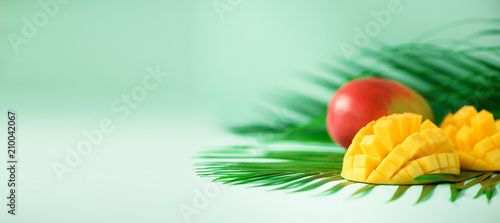 Exotic mango fruit over tropical green palm leaves on turquoise background Fototapet