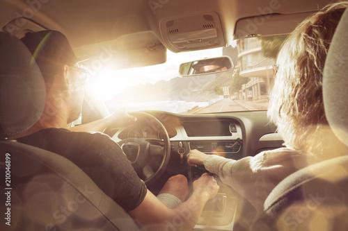 Junges Pärchen im Auto bei Sonnenuntergang Tableau sur Toile